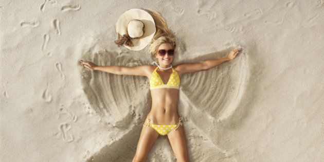 Young attractive woman playfully creating a Sand Angel in the sand on