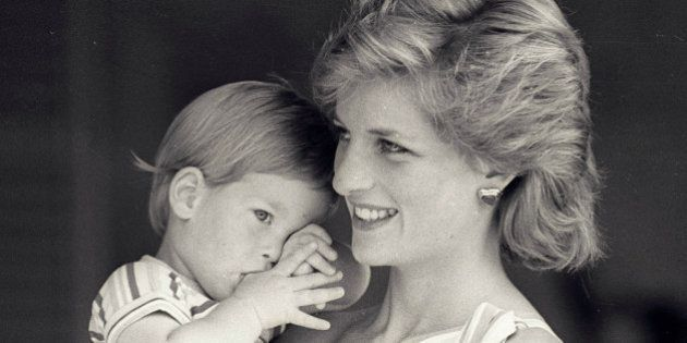 Young Prince Harry tries to hide behind his mother Princess Diana during a morning picture session at...