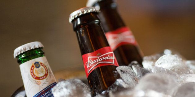 Bottles of Budweiser beer, brewed by Anheuser-Busch InBev NV, right, and a bottle of Peroni beer, brewed...