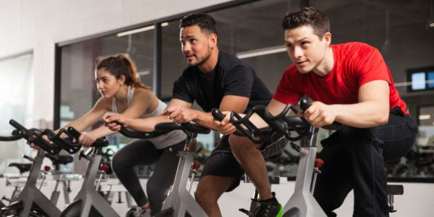 Three young people doing some cardio and acting all focused during their spinning