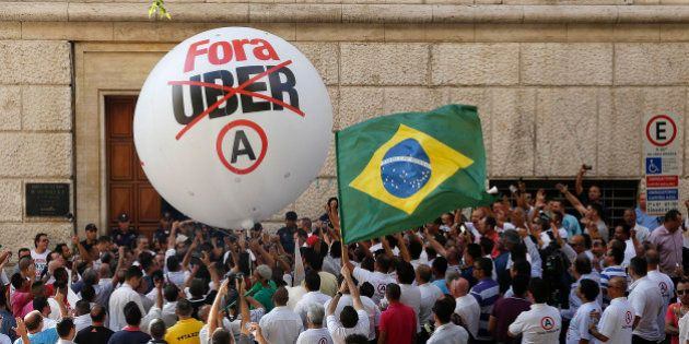 Taxi drivers protest against the ride-booking company Uber outside the City Hall in downtown Sao Paulo,...