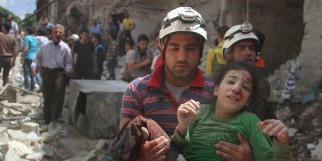 ALEPPO, SYRIA - APRIL 28: (EDITORS NOTE: Image depicts graphic content.) A man carries injured girl after...