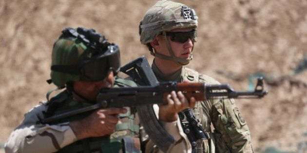 TAJI, IRAQ - APRIL 12: A U.S. Army trainer watches as an Iraqi recruit fires at a military base on April...