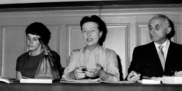 Writer Simone de Beauvoir, center, speaks during a news conference in Paris, Nov. 27, 1961 with lawyer...