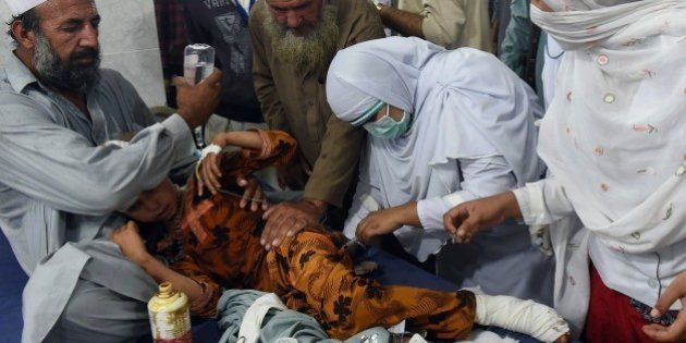 Pakistani paramedics treat a girl injured in an earthquake at a hospital in Peshawar on October 26, 2015....
