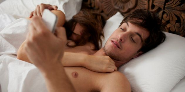 Couple in bed texting whilst girlfriend is