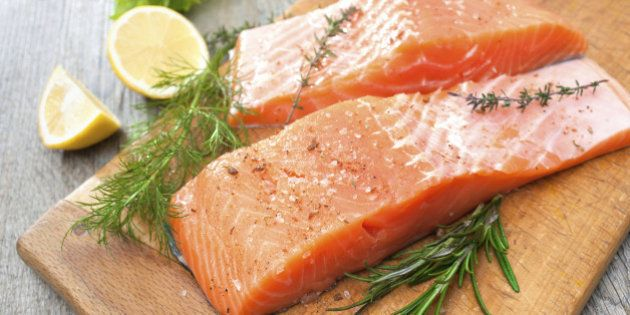 Raw salmon fish fillet with fresh herbs on cutting