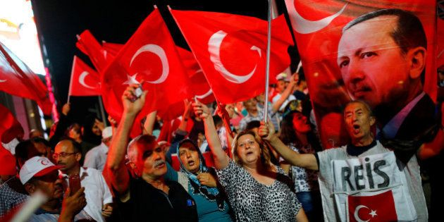 People shout slogans and wave Turkish national flags as they have gathered in solidarity night after...