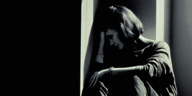 Woman sitting in corner, head resting on hand