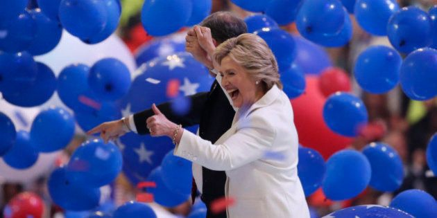 Democratic presidential nominee Hillary Clinton enjoys the balloon drop with her vice presidential running...