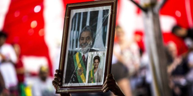 A protester holds a photograph of Luiz Inacio Lula da Silva, Brazil's former president and current chief...