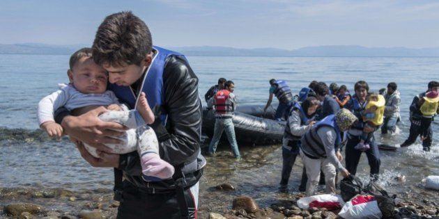 A refugee from Afghanistan carries a baby on arrival on the shores of Lesbos near Skala Skamnias, Greece...