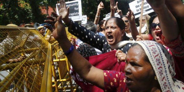 Demonstrators from the All India Democratic Women's Association (AIDWA) shout slogans and hold placards...