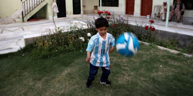 Five year-old Murtaza Ahmedi, an Afghan Lionel Messi fan, wears a shirt signed by Barcelona star Lionel...
