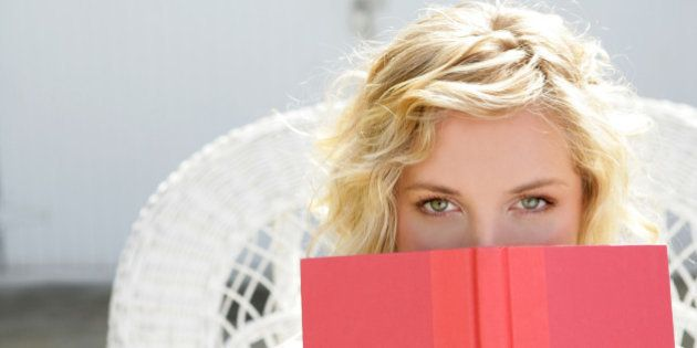 Young woman peeking over open book.