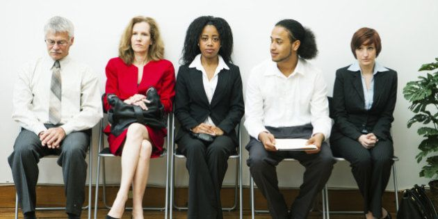 A diverse group of people sitting in a waiting