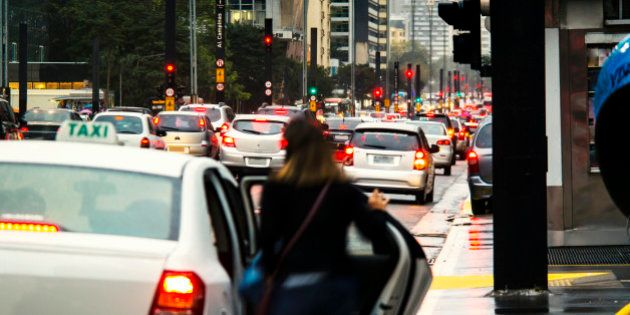 A woman taking a cab at São Paulo Avenue. It was a rainy day and many cars on the street. Entering in...