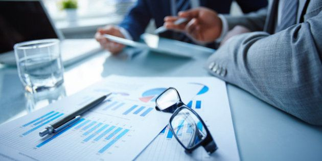 Image of eyeglasses and financial documents at workplace with businessmen discussing ideas near