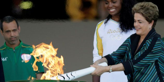 Brazil's President Dilma Rousseff (R) lights a cauldron with the Olympic Flame next to Fabiana Claudino,...