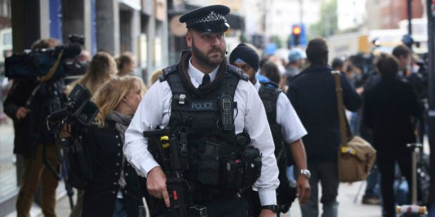 Armed police officers patrol at the scene of a knife attack in Russell Square in London, Britain August...