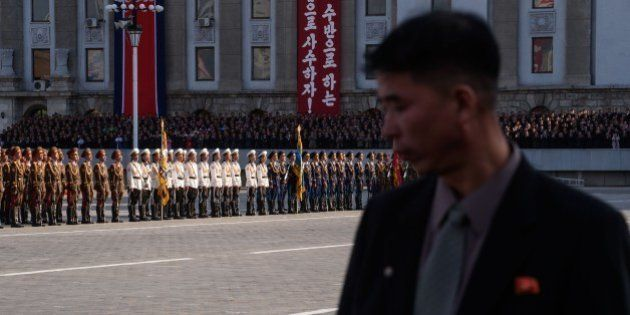 A minder stands before North Korean soldiers at the start of a mass military parade at Kim Il-Sung square...