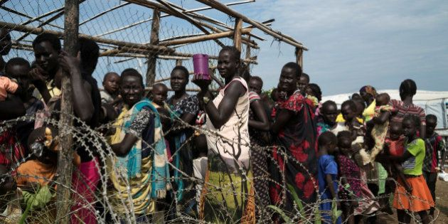 South Sudanese women and children queue to receive emergency food at the United Nations protection of...
