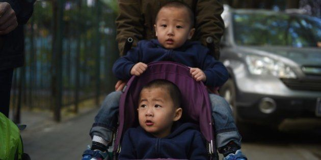 Two brothers are pushed in a pram in Beijing on October 30, 2015. China announced the end of its hugely...