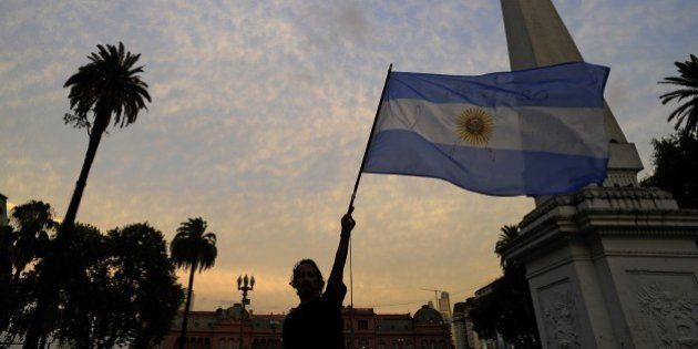 A man holds up an Argentinian flag during a demo at Mayo square, in Buenos Aires on January 19, 2015,...