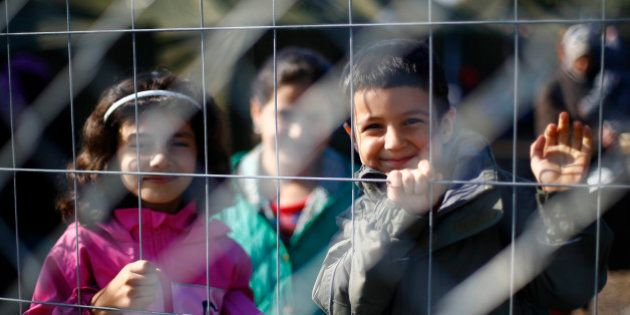 Children smile into the camera behind a fence in a temporary holding center for migrants near the border...