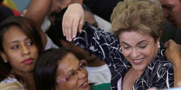 Brazil's President Dilma Rousseff is greeted by members of social movements after a signing ceremony...