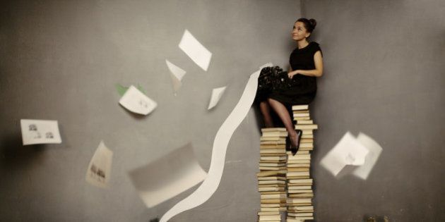 'Young woman sitting on the books and typing, toned