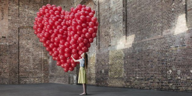 Woman in empty warehouse hugging red heart made of