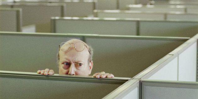 Older man hiding behind office