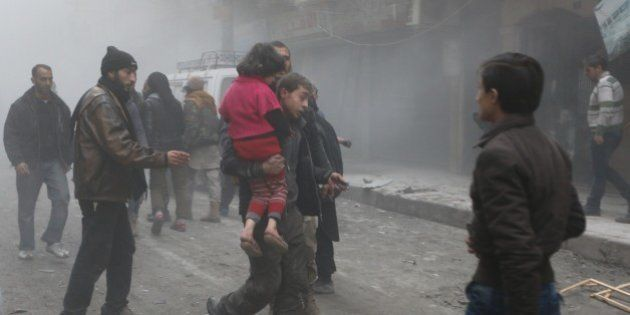 ALEPPO, SYRIA - JANUARY 21: Man carries his child on the street in cloud of dust after the Russian airstrikes...
