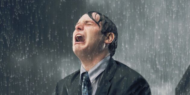 Businessman crying in heavy rain, cityscape in