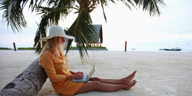 VILLINGILI, ADDU ATOLL , MALDIVES - SEPTEMBER 27: Woman sitting on Villingili beach, working with a notebook...