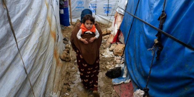 In this picture taken Monday, Jan. 4, 2016, a Syrian refugee woman carries her baby on her back as she...