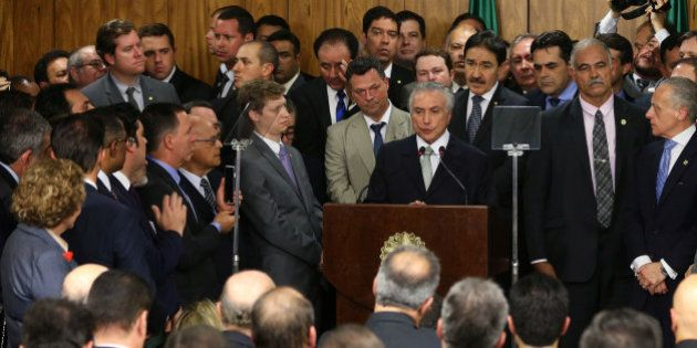Brazil's interim President Michel Temer (at podium) addresses his newly sworn-in ministers (standing...