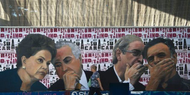 A woman walks past a mural depicting the president of the Brazilian lower house of Congress Eduardo Cunha (2-R) speaking with the president of the Brazilian Social Democracy Party (PSDB) Aecio Neves (R) as if they were conspiring against Brazilian President Dilma Rousseff (L), who is depicted speaking with Vice-President Michel Temer, at Paulista Avenue in Sao Paulo, Brazil on April 19, 2016.Brazil woke Monday to deep political crisis after lawmakers authorized impeachment proceedings against President Dilma Rousseff, sparking claims that democracy was under threat in Latin America's biggest country. / AFP / NELSON ALMEIDA        (Photo credit should read NELSON ALMEIDA/AFP/Getty Images)