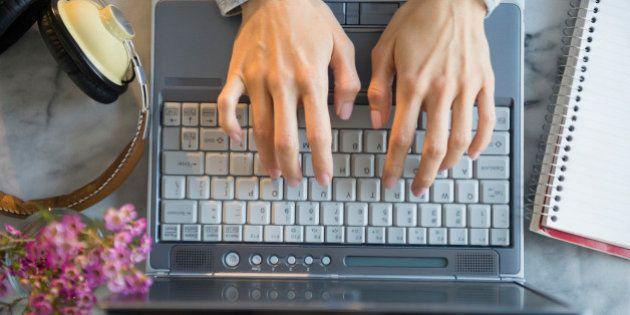 Mixed race woman using laptop at