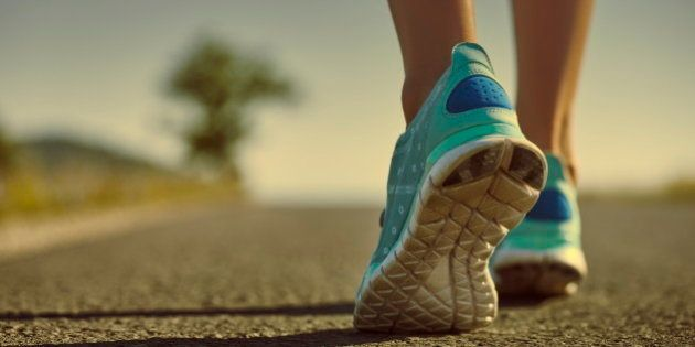 Closeup of athlete female feet in running shoes jogging on the road early in the morning. Healthy