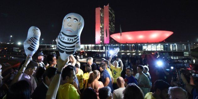 Protesters hold inflatable dolls depicting former Brazilian President Luiz Inacio Lula da Silva during...