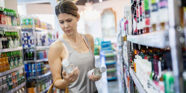 Woman reading labels on bottles in grocery