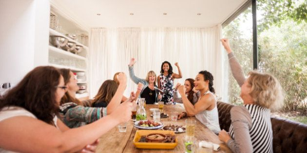 Mixed group of women gathered and sitting at a large table, smiling and raising their fists in a display...