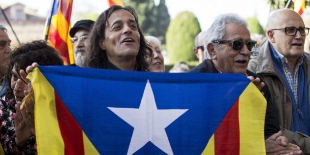 BARCELONA, SPAIN - NOVEMBER 09: Pro-independence activist holds a Catalan flag during the debate about...