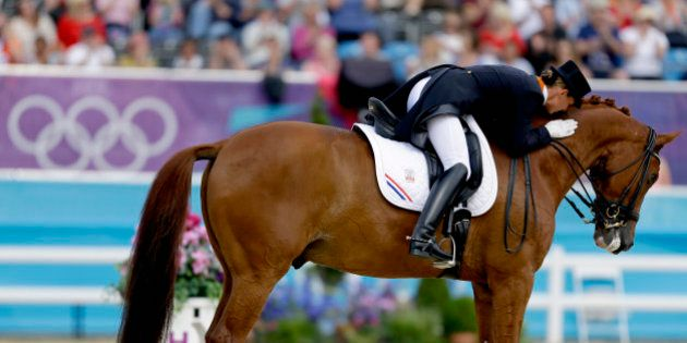 Adelinde Cornelissen, of the Netherlands, pats her horse Parzival, after competing in the equestrian...