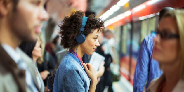 Woman listening to headphones in train