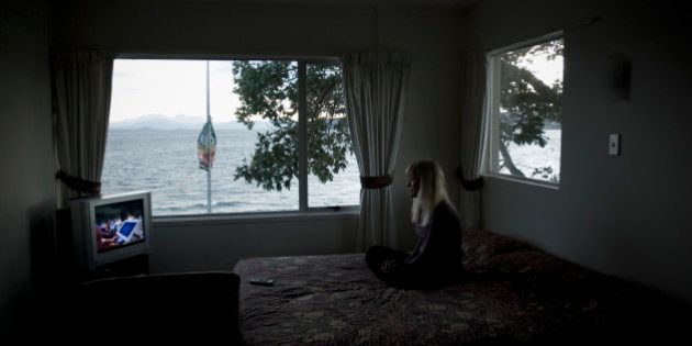 A woman watches tv in her hotel room in Lake Taupo, New