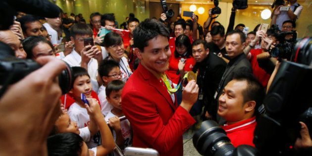 Singapore Olympic gold medallist swimmer Joseph Schooling shows his medal to fans during a homecoming...