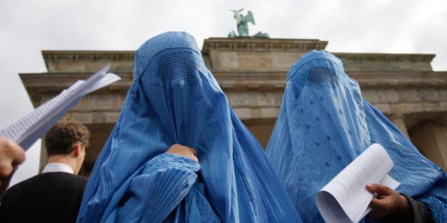 Protestors dressed in traditional burqa garments attend a demonstration against the deployment of the...